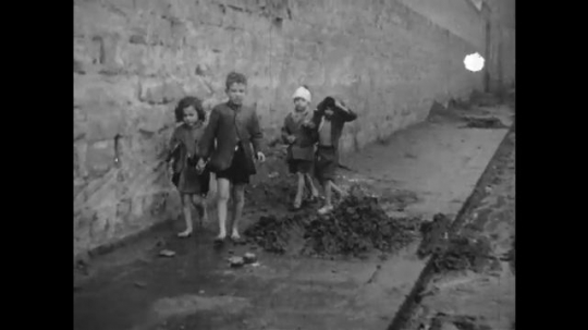 Europe 1940s:  children in bandages and worn clothes walk through street. Orphans and street children. Man walks across street. Children in mud and rags