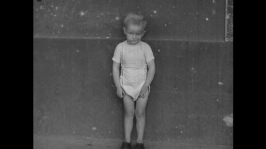 Europe 1940s: boy stands by wall. Boy rocks back and forth. Girl leans on wall. Boy stands in orchard and cries.