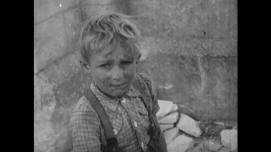 Europe 1940s: boy in street. Boy cares for young children in cart. Children run down steps of derelict building