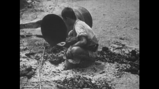 Europe 1940s: children search for food on streets, rubble sites, and in bins. Child smokes on derelict site