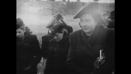 Europe 1940s: people walk to funeral in black clothes. People lay flowers on graves.