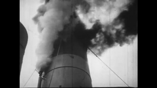 Europe 1940s: supplies loaded onto ship in cargo nets. Men carry supplies in sacks on shoulders. Smoke over ship chimney.