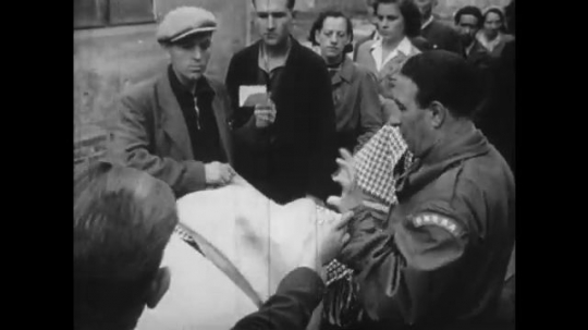 Europe 1940s: sign on wall. People receive food supplies. Man bangs hammer. Lady gives blanket to elderly lady. People eat food.