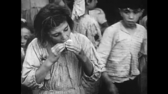 Europe 1940s: child eats bread. Hand feeds rice to baby. Children receive food. New shoes on child