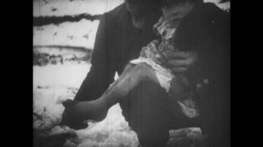 Europe 1940s: man holds child by fire. Street children in street. Child cries. Children hug each over after war