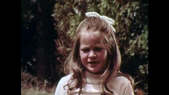1970s: UNITED STATES: girl speaks. Boys talk on log. Man talks to children