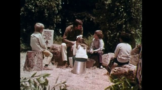 1970s: UNITED STATES: man speaks to children in woods. Close up of boy's face. Close up of man's face