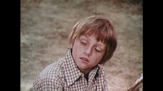 1970s: UNITED STATES: boy speaks in forest. Tree falls in woods. Children fish by river. Tent and camp in woods