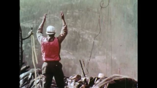 1970s: UNITED STATES: man waves at helicopter. Rangers put out forest fire. Trees damaged in fire. Helicopter sprays water on fire