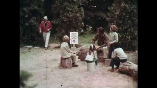 1970s: UNITED STATES: man arrives at camp. Men speak to children.