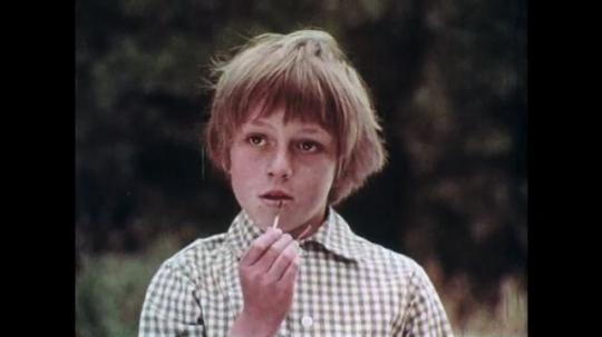1970s: UNITED STATES: boy holds match. Boy breaks match in half. Child speaks. Man listens