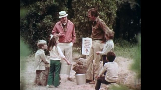 1970s: UNITED STATES: men talk with children in forest. Man smokes pipe