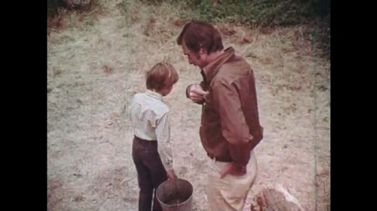 1970s: UNITED STATES: man gives matches to boy. Boy speaks to man. Boy carries bucket. Sign in forest