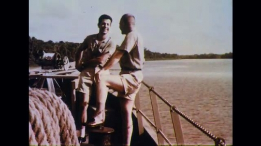 BRAZIL 1960s: Men smiling and talking on ship. Plants in river. Scientists taking water samples. Person swimming in river.