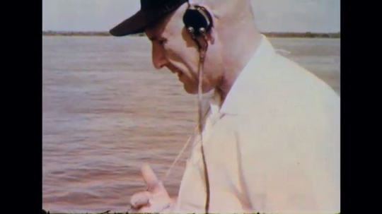 BRAZIL 1960s: Man on ship deck wears headphones and holds clicker. Diagram of boat on river illustrating depth measurements and ship movement.