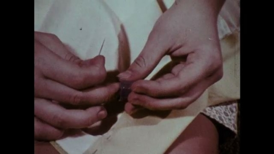 1970s: Hands attach thimble to finger. Hands sew. Girl brushes teeth. Man walks toward car.