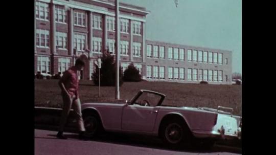 1970s: Boy enters car. Boy drives through stop sign.