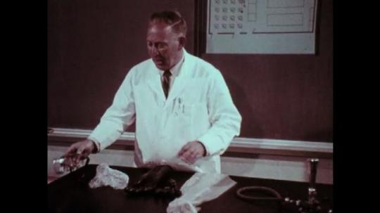 1970s: Man demonstrates protective equipment. Boy checks wristwatch.