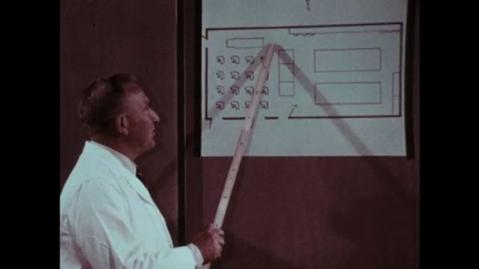 1970s: Man points to map of classroom. Man speaks. Finger points to map of classroom.