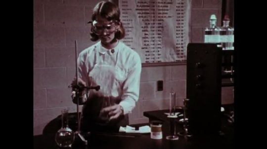 1970s: Girl adjusts glassware with clamp. Hands insert glass tube into stopper.