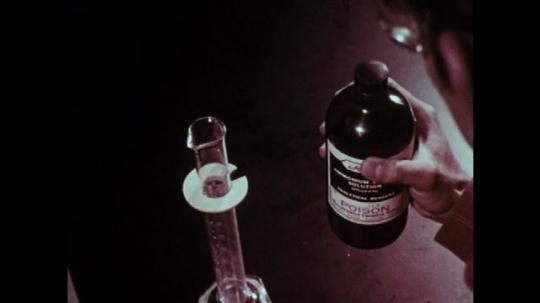 1970s: Boy observes bottle. Boy opens bottle. Hand sets bottle on table.