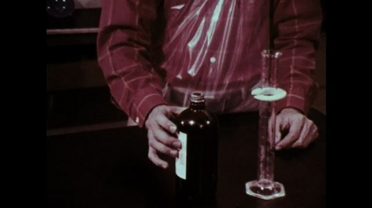 1970s: Hands pour chemical into graduated cylinder.