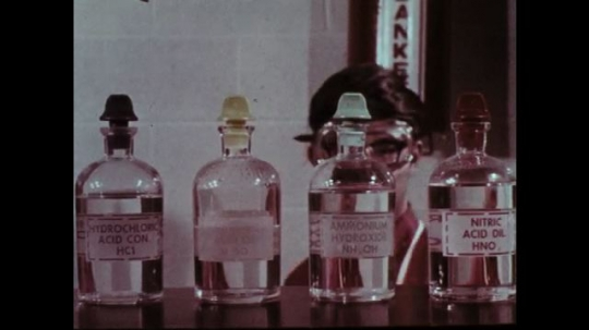 1970s: Boy takes chemical bottle from shelf. Man observes students. Students work at laboratory tables. Man observes boy.
