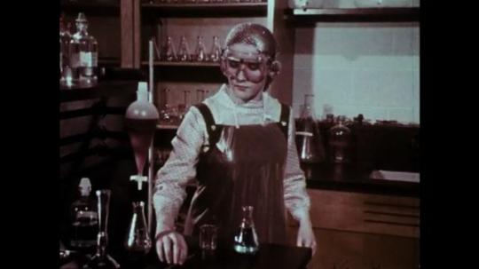 1970s: Girl picks up glass tube. Man observes girl. Girl places glass tube in beaker. Boy rushes to reprimand girl.
