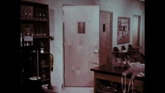 1970s: Two men enter classroom. Teacher greets men. Three men don safety gear.
