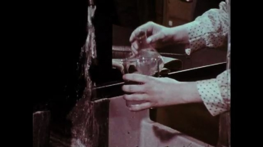 1970s: Hands pour chemical into beaker. Hands wash beaker with brush. Students return to classroom. Nurse holds baby.