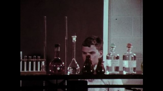 1970s: Boy browses shelf of chemistry equipment. Boy adjusts safety goggles.