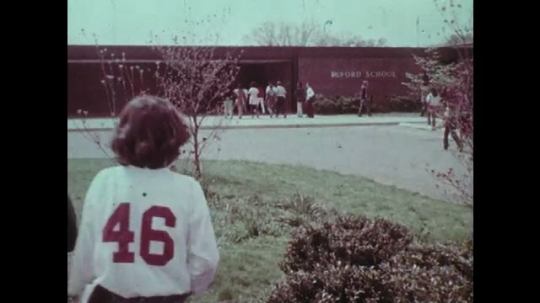 1970s: UNITED STATES: students arrive at school. Students enter building. Students walk across ground. Students by lockers
