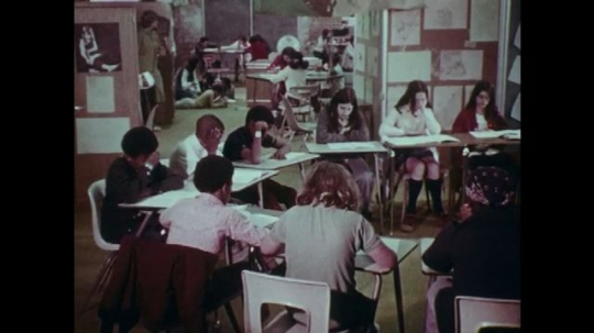 1970s: UNITED STATES: students sit in semi circle in classroom. Students study at desks.