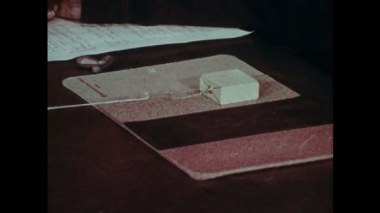 1970s: UNITED STATES: hand pulls box across table. Children work in small group at table. Students perform experiment.