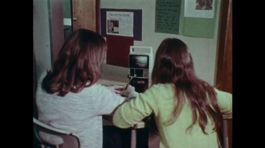 1970s: UNITED STATES: students watch small monitor in lesson. Children write notes.