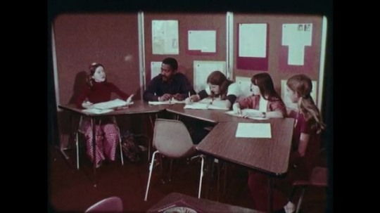 1970s: UNITED STATES: students work together at table. Students discuss question with teacher