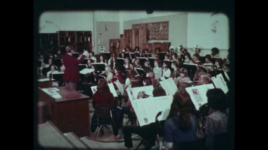 1970s: UNITED STATES: students play instruments in orchestra practice at school.  Teacher conducts band