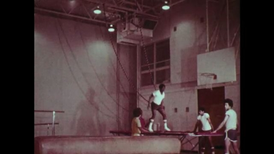 1970s: UNITED STATES: students in trampolining class. Students flip over horse in gym class