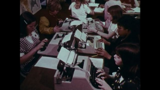 1970s: UNITED STATES: students work on typewriters in class. Girl sews material in class. Girls in needlework class