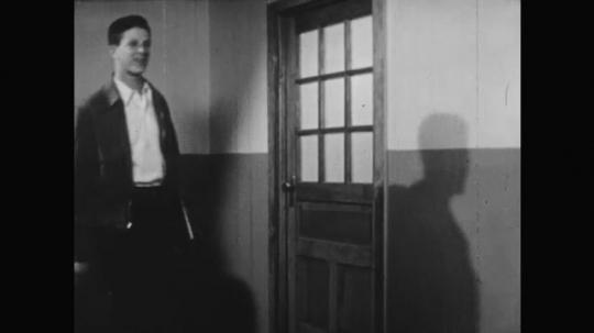 1950s: teenage boys and girls walk, carry textbooks and talk in school hallway near classroom door.
