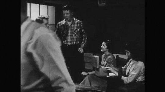 1950s: teenage boy blows on fingers, rubs hand on shirt and talks to boy and girls in chairdesks at school classroom.