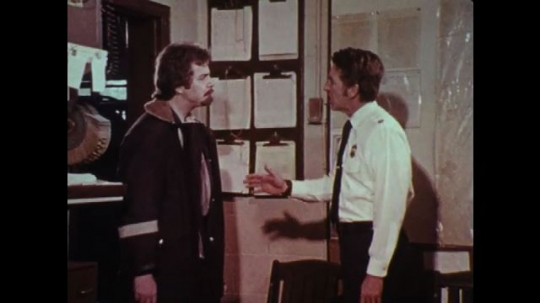 1970s: UNITED STATES: police man speaks with boss in station office. Fire chief argues with employee. Men in office.
