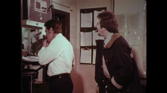 1970s: UNITED STATES: men argue in office, Police men in station office.