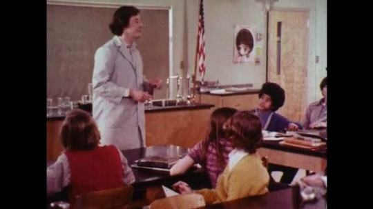 1970s: Male student raises hand, male teacher lectures science classroom,
