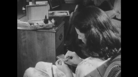 1940s: Girl removes polish from nails. Hand rubs cotton over fingernails. Girl removes fingernail polish. Boy checks fingernails. Boy opens box on sink.