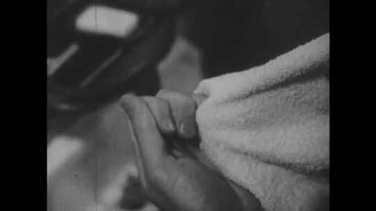 1940s: Hands polishes fingernails with cloth. Foot on a low stool. Hands clip toenails.