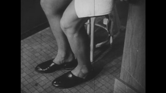 1940s: Feet step into slippers. Man walks to bathroom sink. Man combs hair. Woman pass by mirror. Women check hair in mirror.