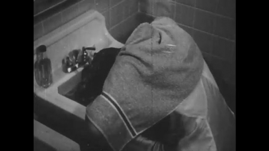 1940s: Girl washes hair at bathroom sink. Girl rinses hair in bathroom sink. Hand reaches for bottle. Girl pours liquid from bottle into sink. Girl rinses hair in bathroom sink.