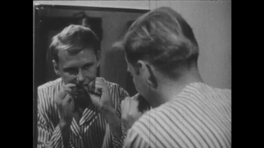 1940s: Boy flosses teeth in mirror. Dentist examines boy