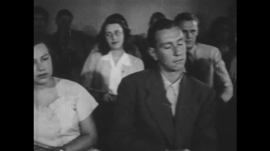 1940s: Boy in casual attire sits at desk. Girl in casual attire sits in classroom. Girl removes high heels and adjusts feet. Girl squirms in classroom desk.